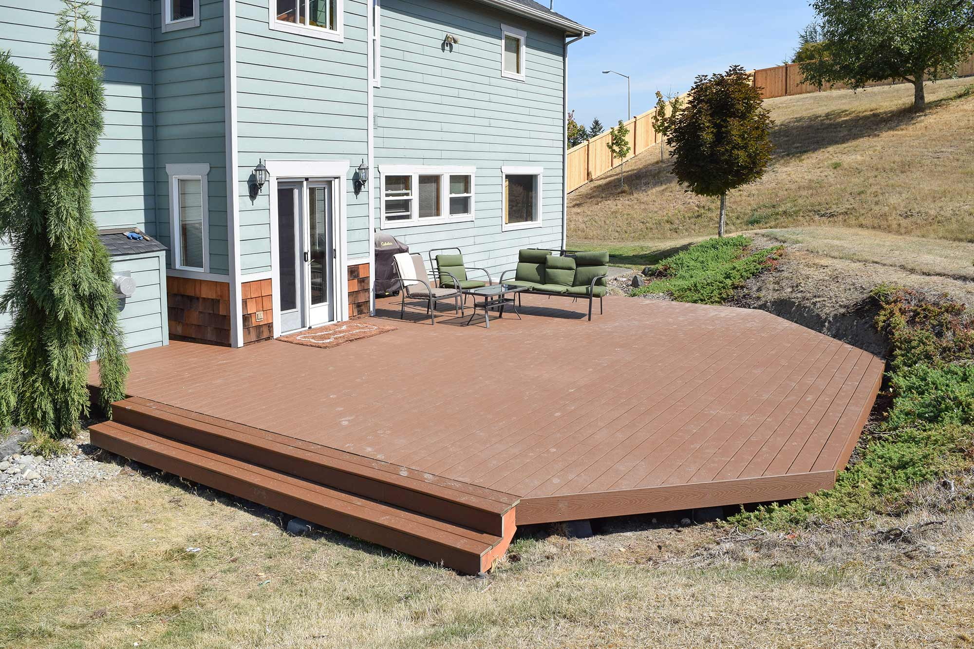 AJB Landscaping & Fence installed this Trex composite deck with angled corners to contour the existing grade of the hill.
