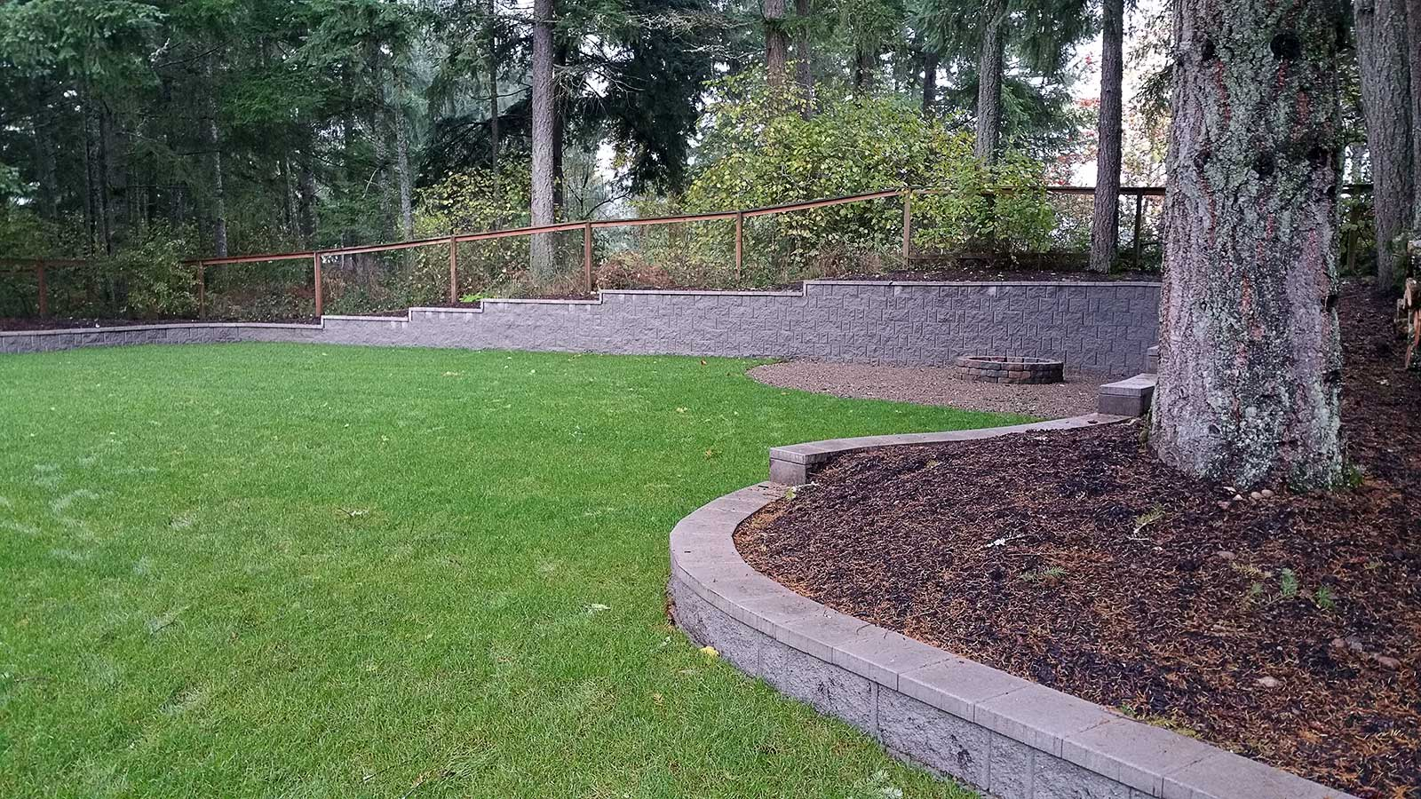 The Vanquathem's backyard now features a new retaining wall, fresh landscaping, a much larger law with new sod and a UG sprinkler system. Point to the image to see how it looked before.