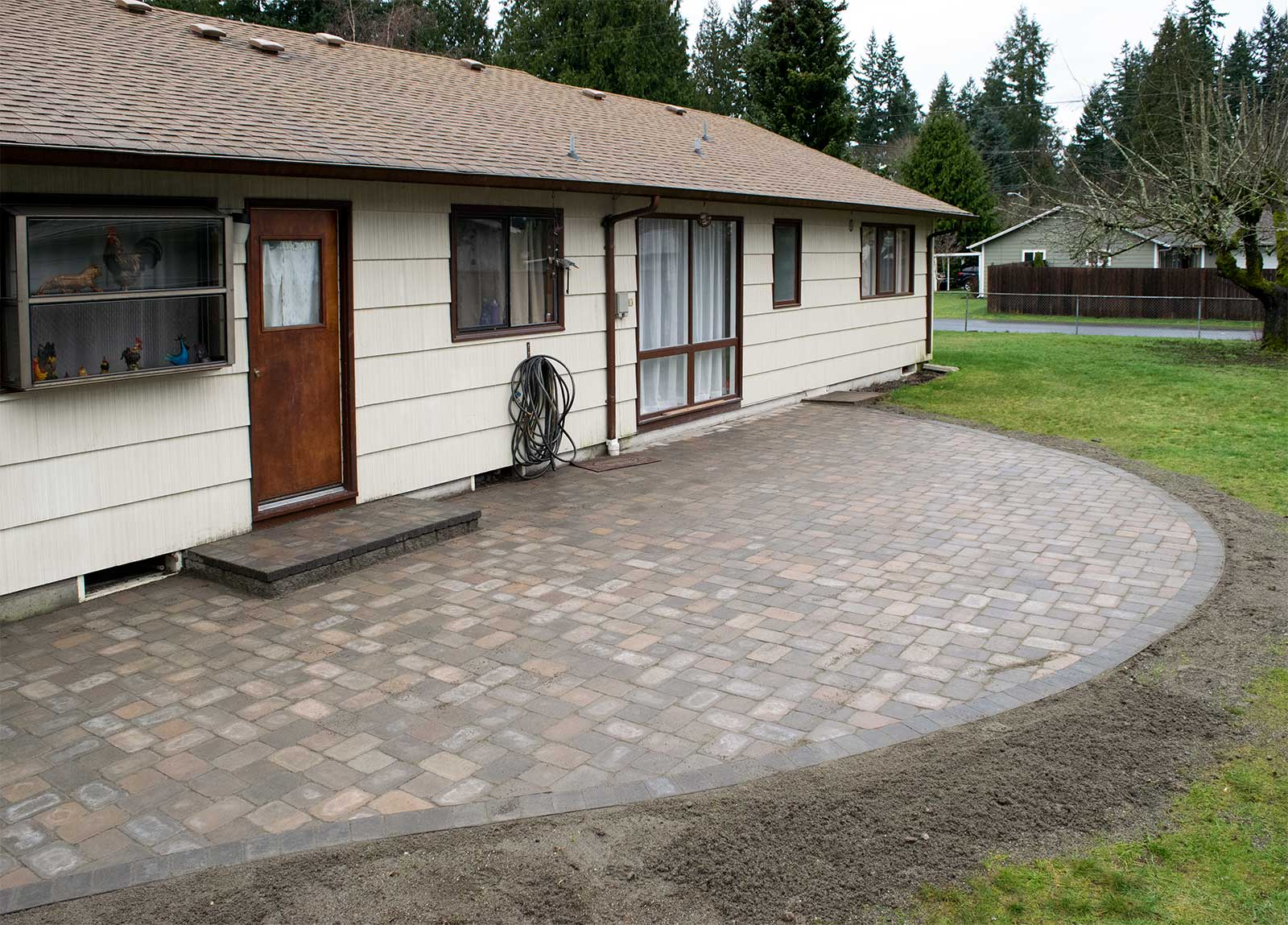 Roca style tumbled paver patio brings new life to this Lacey rambler's backyard. Point to the picture to see how it looked before.