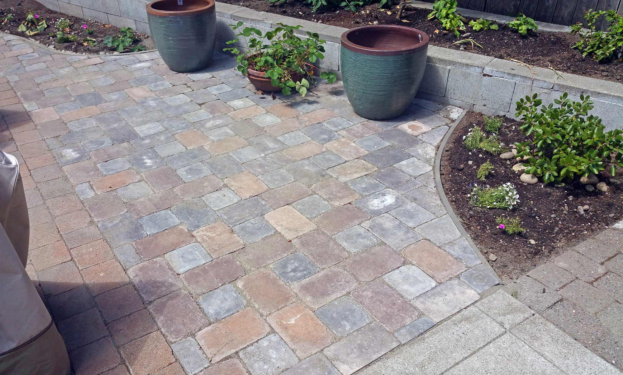 We extended the existing paver patio, integrating landscape beds and meeting a concrete slab.