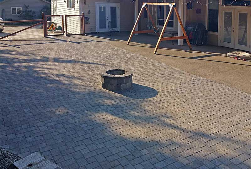 "AJB Landscaping & Fence extended this home's backyard concrete slab with a Western Interlock paver patio and fire pit. Point to the photo to see the ""before"" picture."