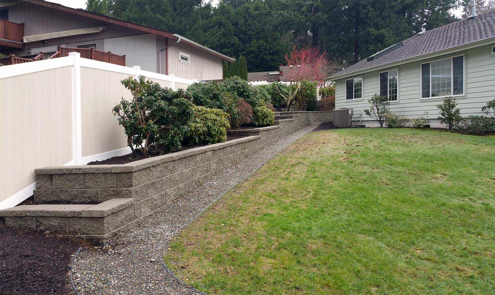 Tiered retaining wall with complementing vinyl fence. Point to the image to see how it looked before the transformation.
