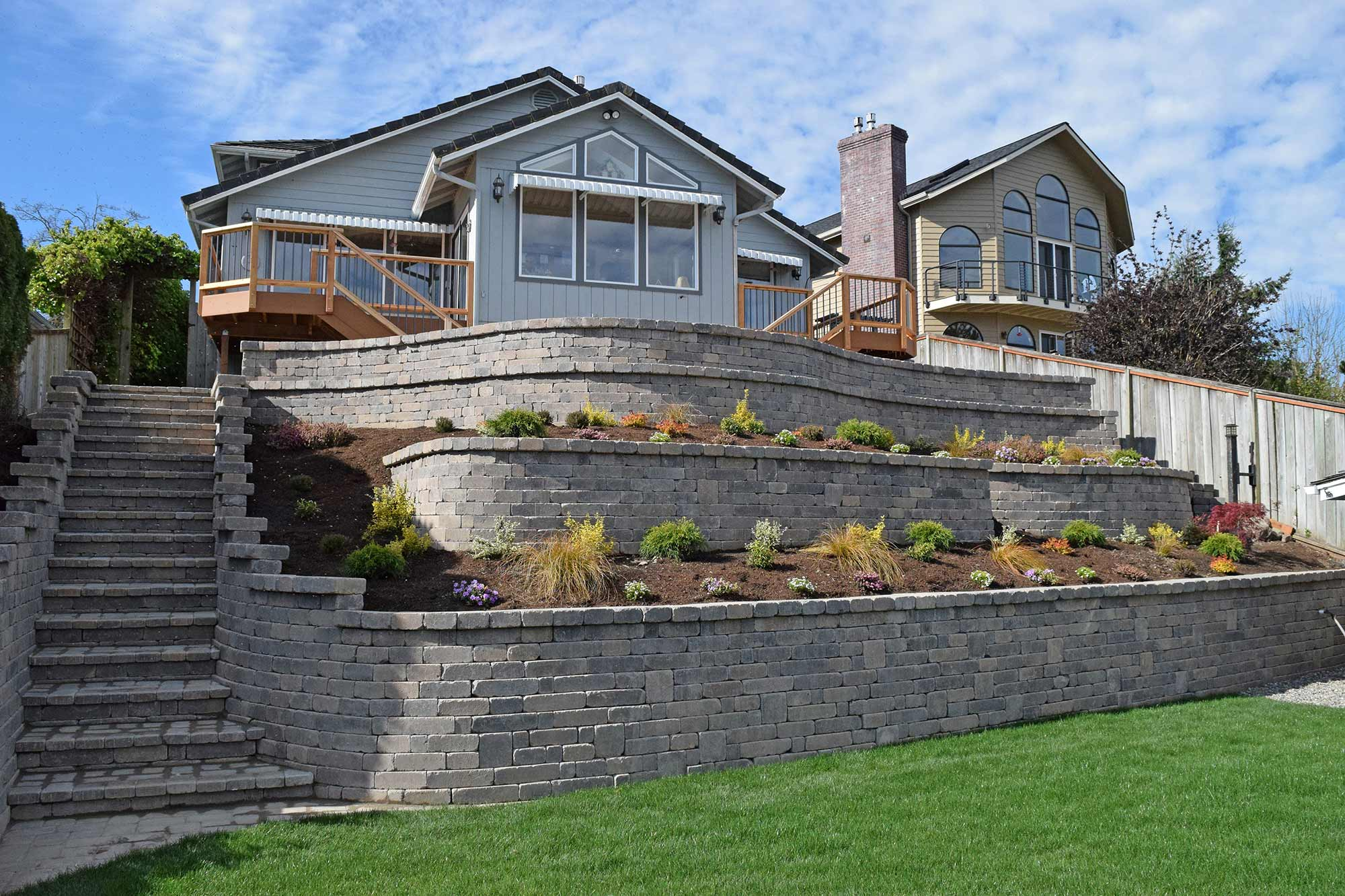 This massive, 4-tier retaining wall includes an integrated stairway, landscaping and a paver patio above the top tier.