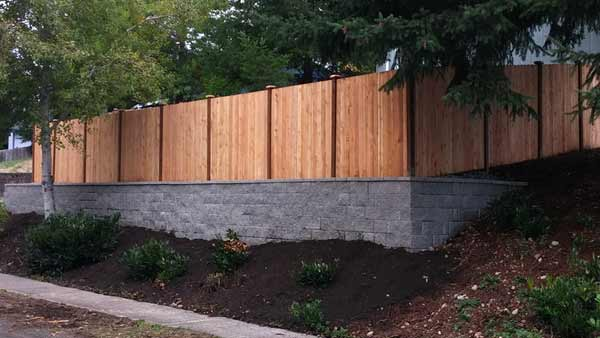 Fence and retaining wall with capstones.
