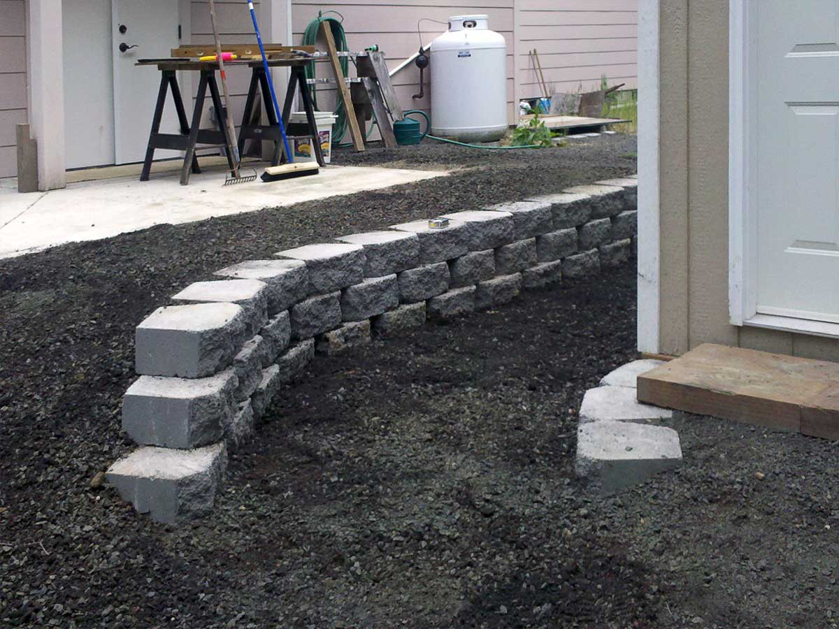 Finished small retaining wall protects against erosion and separates the shed from the house.